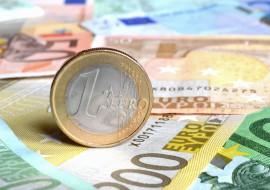 Eine Euro Münze auf vielen Geldscheinen